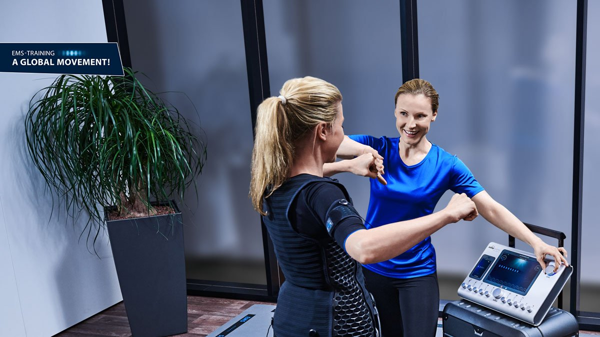 woman trains with personal trainer at a mobile miha bodytec II station